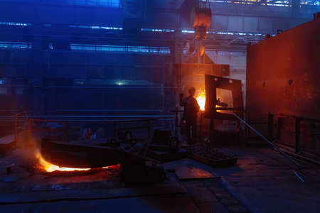 Worker operates metal casting process in metallurgical plant. 版權商用圖片