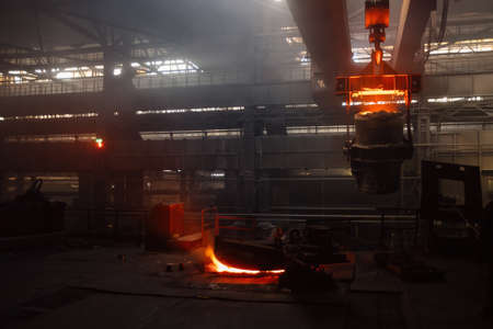 Iron casting and the foundry. Overhead crane with ladle with molten metal at metallurgical factory.