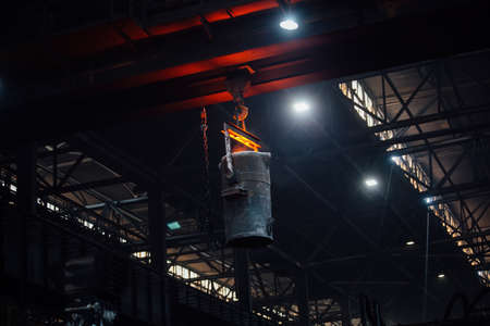 Iron casting at the foundry. Overhead crane with ladle with molten metal at metallurgical factory.