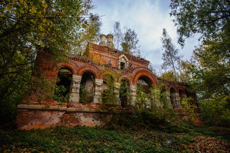 Old ancient abandoned church ruins overgrown by plants.