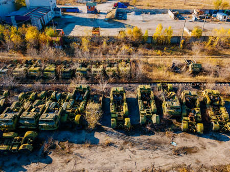 Old rusty broken Russian military cars for scrap metal in industrial area, aerial view.