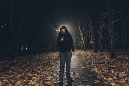 Sad man alone walking along the alley in night foggy park with mobile phone.