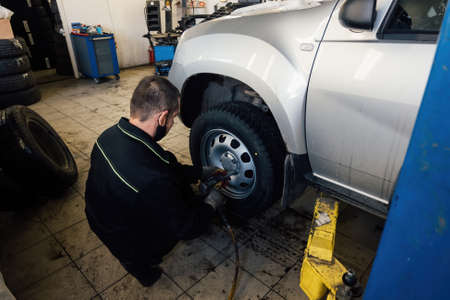 Mechanic changing car wheel in auto service workshop.