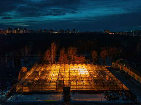 Glowing modern glass greenhouse in winter night, aerial view.