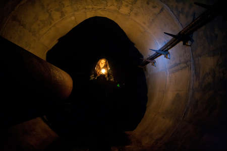 Urban explorer with candle in old vaulted underground tunnel.