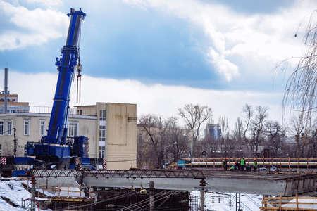 Workers in protective helmets are repairing bridge in Voronezh.