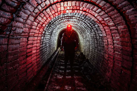 Man in protective suit inside abandoned uranium mine.