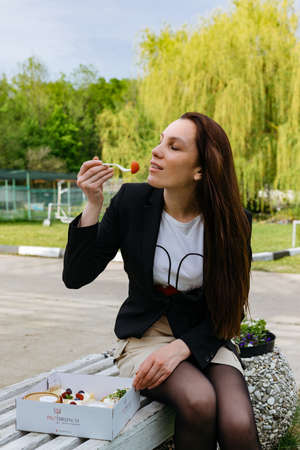 Young beautiful girl having lunch in the park