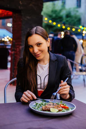 A beautiful young woman eating meal in restaurant.