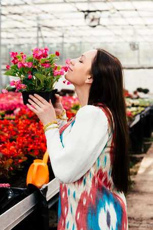 Attractive young woman smelling pink flowers in pot in greenhouse.