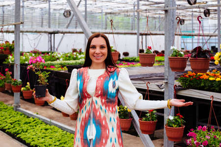 Attractive young woman with flowers in pot in greenhouse, gardening concept.
