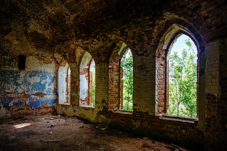 Inside the old ruined red brick church in gothic style.