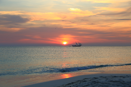 Gorgeous colorful sunset on the Caribbean sea, Unforgettable view of the Aruba landscape. Small boat on horizon line.