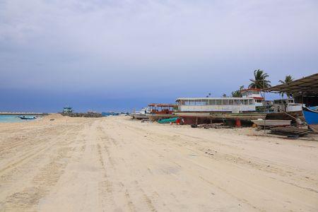 Industrial area on Dhangethi Island, Maldives. Sand road, old boats on blue sky background.