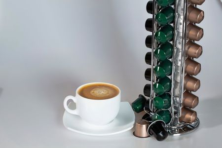 Close up view of carousel holder for coffee capsules and white cup of coffee. Food and drink concept. Beautiful background.