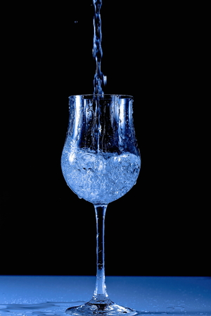 Close up view of splashing water in glass isolated. Beautiful backgrounds in blue.