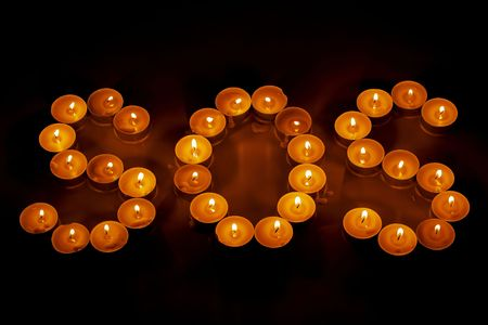 Close up view of SOS sign of tealights. Beautiful backgrounds. Standard-Bild