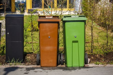 Close up view of typical garbage containers for organig and non-organic garbage sorting near black postbox. Environment concept.