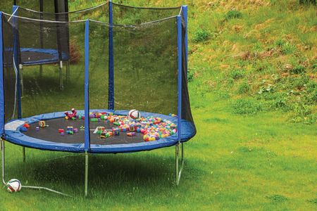 A line of trampolines with safety net mounted on backyards. Activity concept.