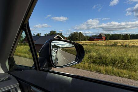 Blick im Seitenspiegel auf nachfahrende Fahrzeuge. Transportkonzept. Schöne Hintergründe. Standard-Bild