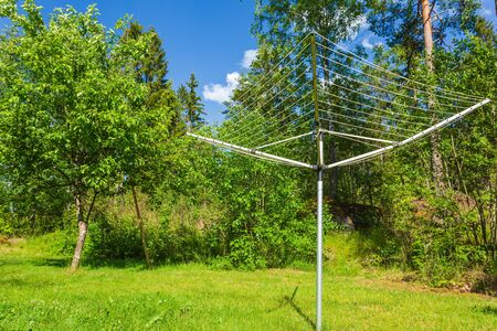 Collapsible outdoor clothes dryer view. Rotary Washing Line Airer Clothes Dryer aluminum. Green trees and blue sky with white clouds background. Stock fotó