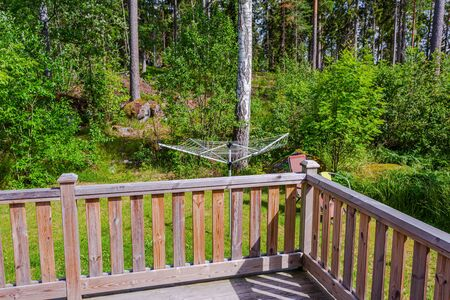 Beautiful view of backyard of private house with old wooden patio and collapsible outdoor clothes dryer view. Gorgeous green nature on summer day. Sweden Europe Stock fotó
