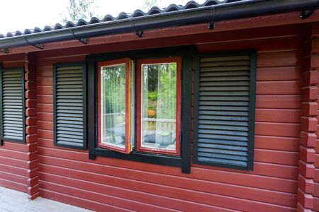Close up view of facade of typical wooden swedish house. Red walls and contrast black windows. Sweden.Europe