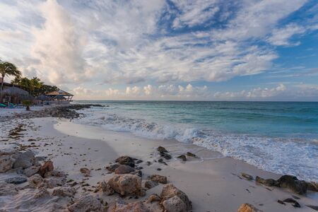 Gorgeous view of atlantic ocean coast line. Turquoise water surface merging with blue sky with white clouds. Aruba island. Caribbean.