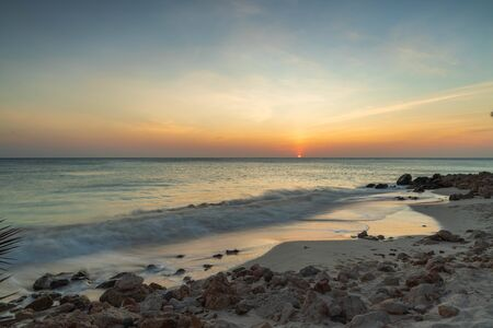 Gorgeous colorful view of sunset on Aruba. Beautiful nature landscape. Rocky coast of Atlanta, Caribbean. Imagens