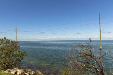 View of the Gulf of Mexico coast line. Power line passing through ground water along highway to Key West, Florida. Beautiful nature landscape backgrounds.