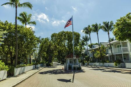 Beautiful view of famous Truman Annex Entrance gate. Beautiful historical buildings and green trees on blue sky background. Key West, Florida. USA