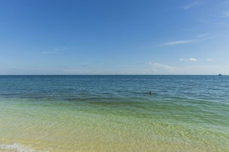 Beautiful view of Atlantic ocean. Blue water surface merging with light blue sky in horizon line. One person is swimming. Key West, Florida. USA