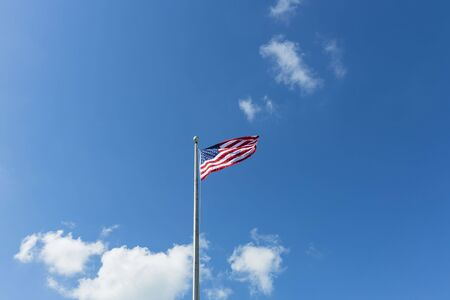 Beautiful view of American flag blue sky with white clouds background.