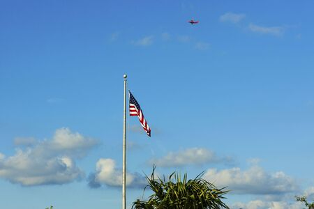 American flag on blue sky with white clouds background. Red aircraft far away in sky.