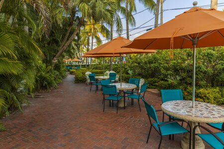 Beautiful view of outdoor tables. Blue chairs and orange umbrellas on green palm trees and blue sky background. Key West, Florida. USA 06092019 Editorial