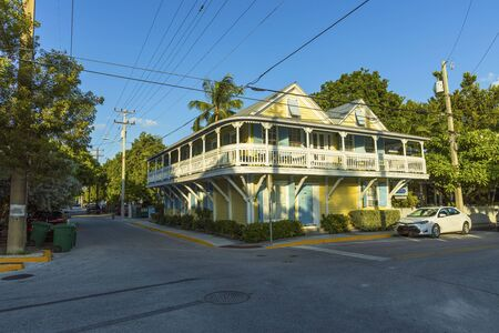 View of one of streets of Key West. Old houses and big green trees on blue sky background. Key West. Florida USA 06092019.