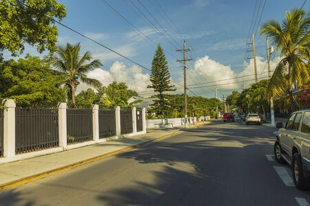 View of one of streets of Key West. Old houses and big green trees on blue sky background. Key West. Florida USA