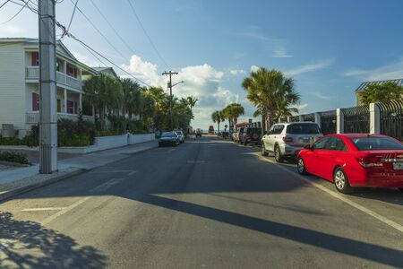 View of one of streets of Key West. Old houses and big green trees on blue sky background. Key West. Florida USA 07092019.