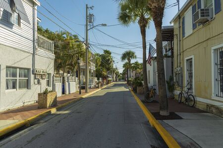 Beautiful street landscape view of one of streets in Key wet, Florida. Light houses and green palm trees on blue sky background.