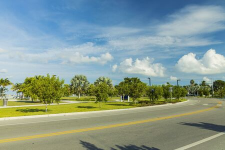 Beautiful view of city landscape. Asphalt road and green tropical trees on blue sky with white clouds background. Key West. Florida USA Imagens
