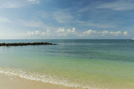 Beautiful view of Atlantic ocean sand beach. Yellow sand turning into dark blue water that merges with light blue sky. Key West, Florida. USA Imagens