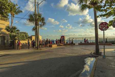 Tourists standing in line in order to take picture at famous tourist attraction Southernmost point. Key West. Florida USA