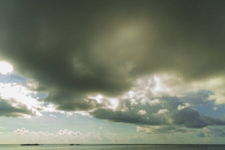 Beautiful view of the blue water of the Atlantic Ocean merging with light blue sky and thunder clouds.