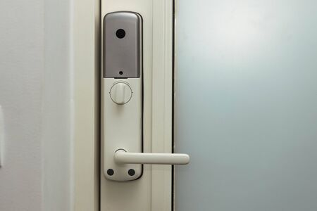 Close up view of an electric combination lock on a white door. Interior design. Beautiful backgrounds.