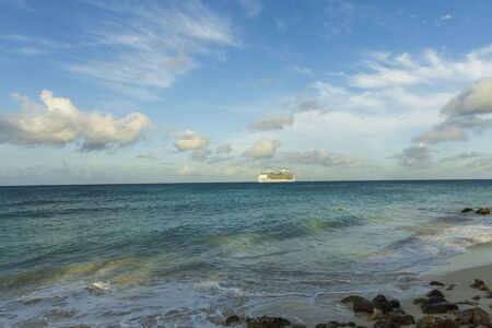 Amazing beauty Atlantic ocean turquoise water surface. Big cruise boat merging with blue sky and white clouds. Aruba island. Unforgettable view.