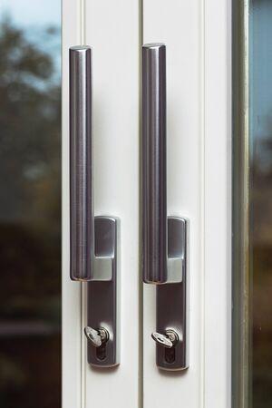 Close up view of steel door handles on glass doors isolated. Interior design concept. Stockfoto