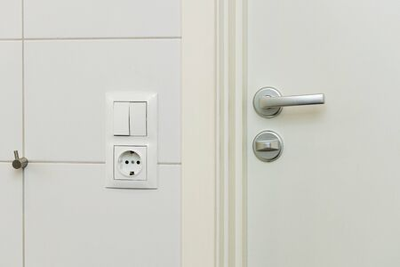 Close up view of power socket and power switch near door handle on white wall and door. Interior design elements concept.