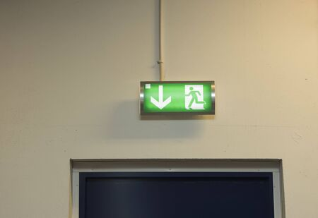 Close up view of green emergency exit plate. Safety concept.