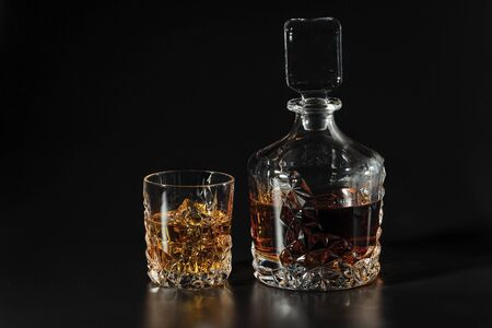 Beautiful view whiskey decanter and glass of whiskey with ice on black background. Beautiful backgrounds. Alcohol concept. Reklamní fotografie