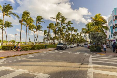 Beautiful landscape view of street of Miami Beach. White buildings and palm trees on both sides of asphalt road on blue sky and white clouds background. USA Miami South Beach. 22092019.
